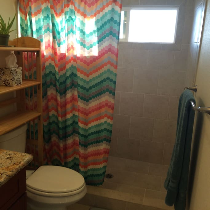 Large shower private shower stall with high window facing ocean
