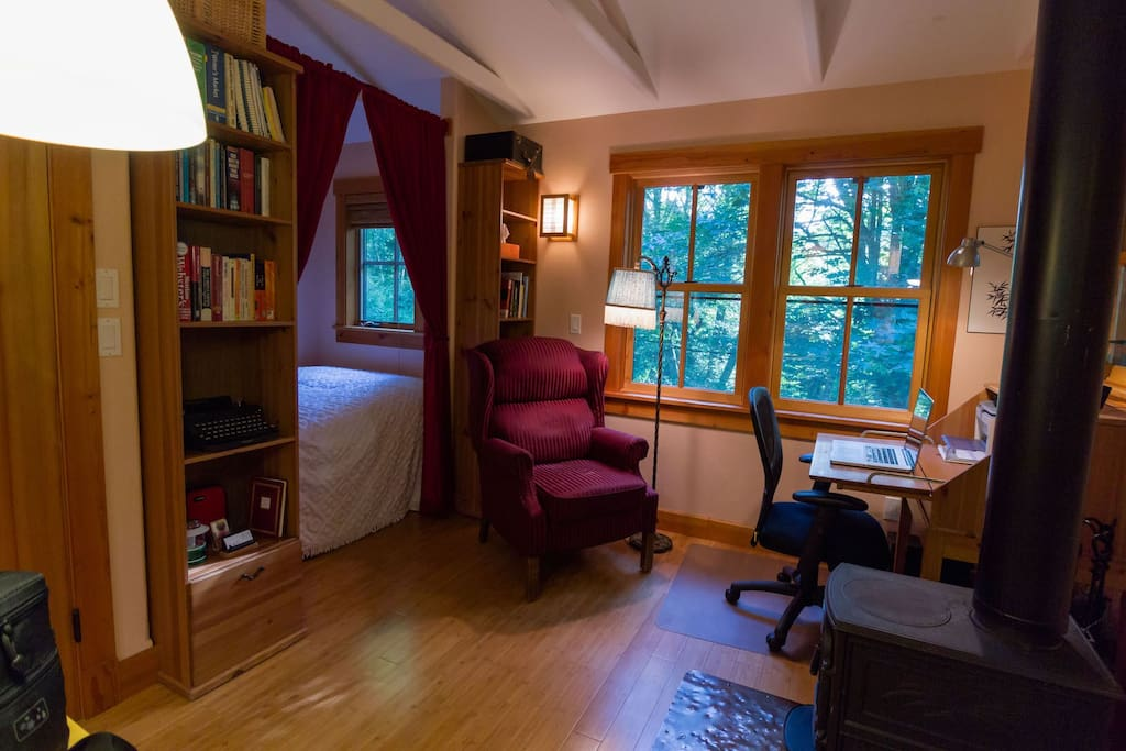 The forest is visible from every window. There are reference books for writers on the bookshelf, and a comfortable wingback recliner to read or write in. (Photo by Camille Meehan)