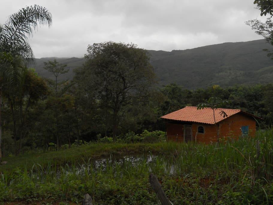 Vista do chalė em dia nublado ao lado Poço de Criação de Peixe