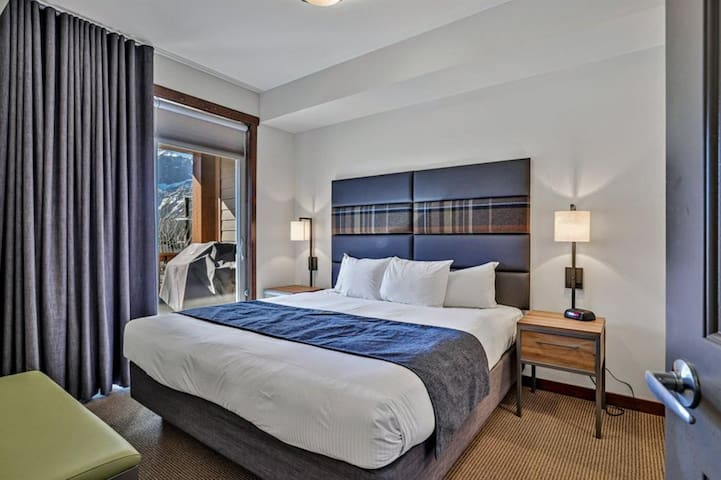 Deluxe bedroom #2 with a king bed and a breathtaking mountain view from the window