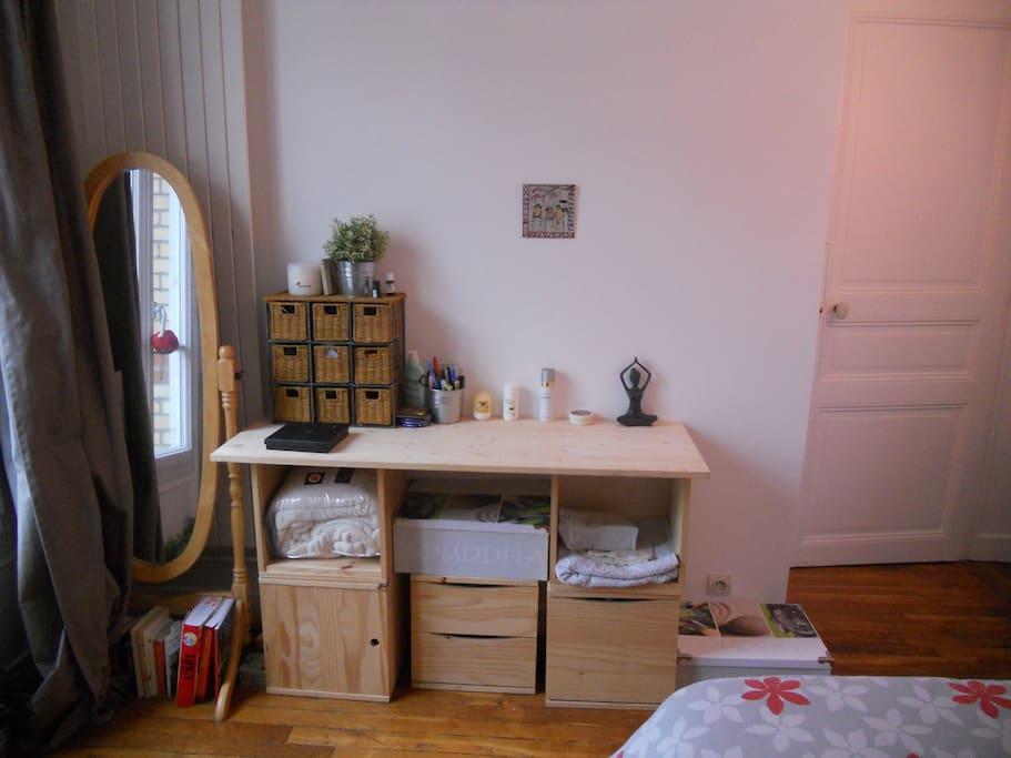 Chambre avec un grand miroir et différents rangements.