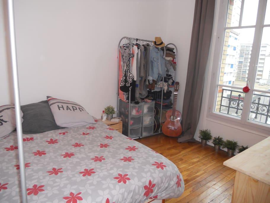 Chambre, un lit deux places avec une penderie et une fenêtre donnant sur le quartier.