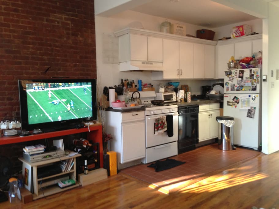 fully equipped kitchen flatscreen wood floor brick walls