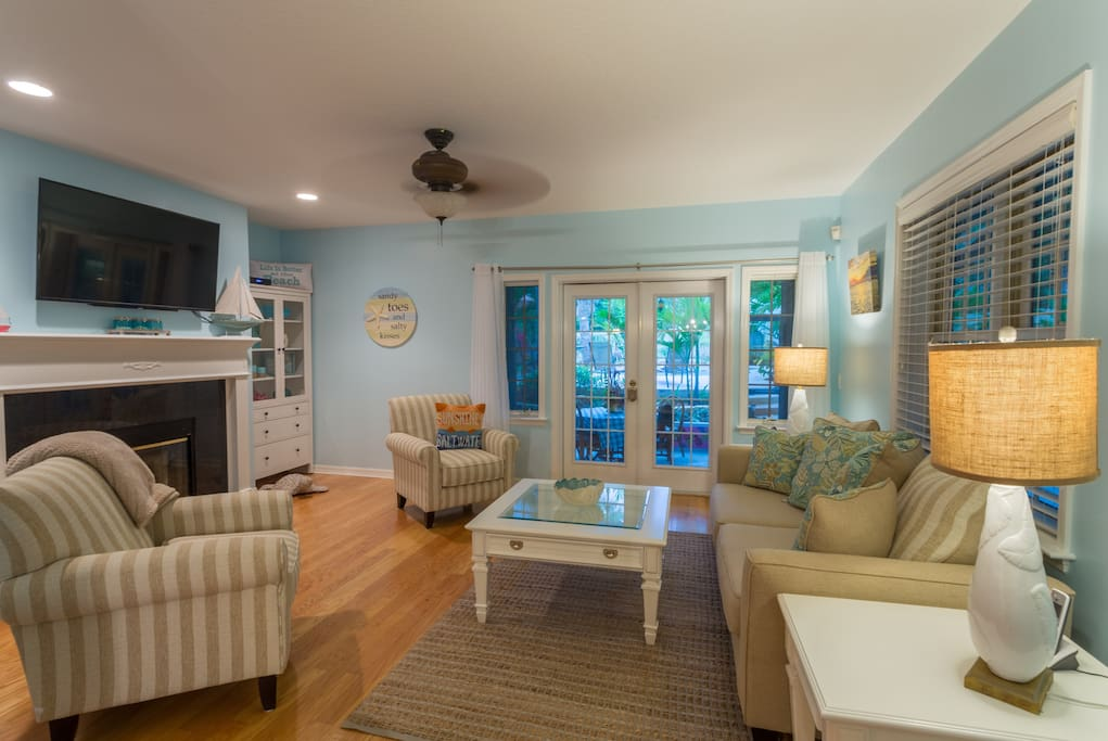 Spacious living room with pull out sofa and access to screened porch and pool