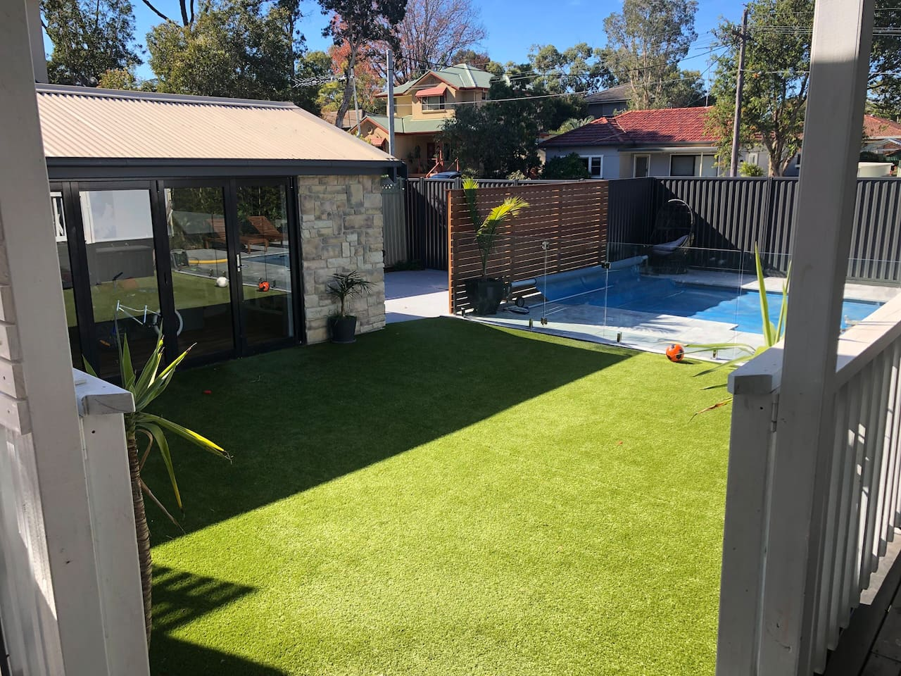 Garden with artificial lawn and kids play room and media room with sofa bed.
