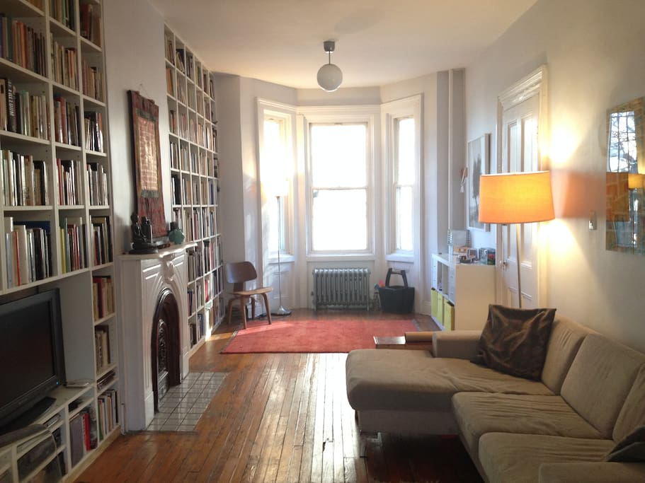 Spacious living-room with books, toys, flat-screen TV and a comfy couch.