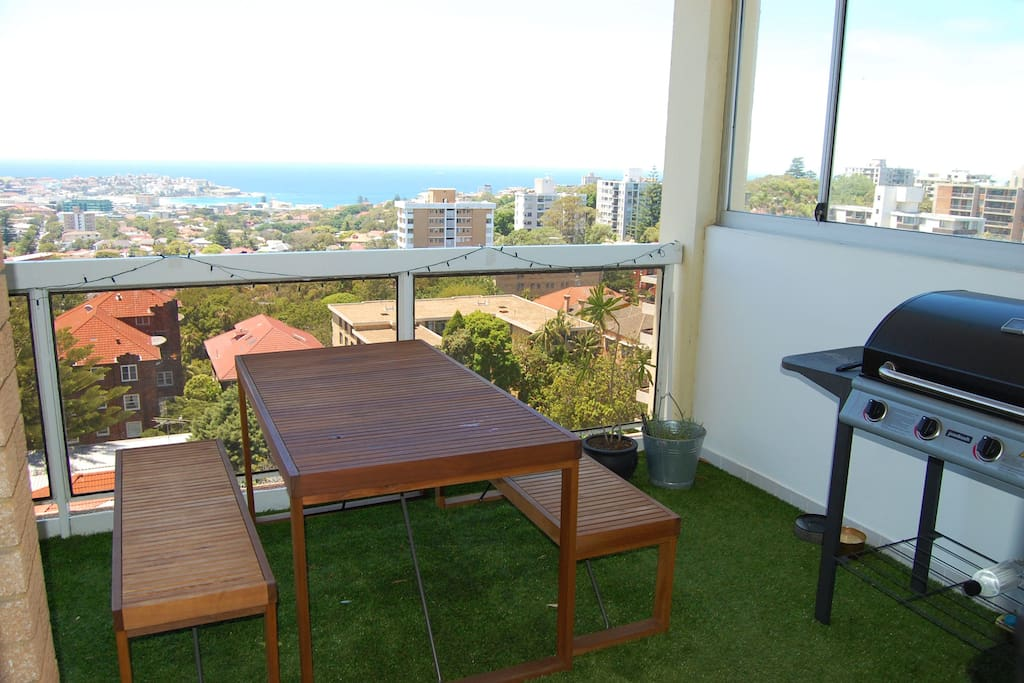 Huge balcony with amazing views over Bondi Beach, with sunbeds, dining table and BBQ.