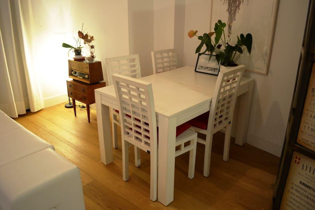 Hay una zona de comedor, con mesa y cuatro sillas