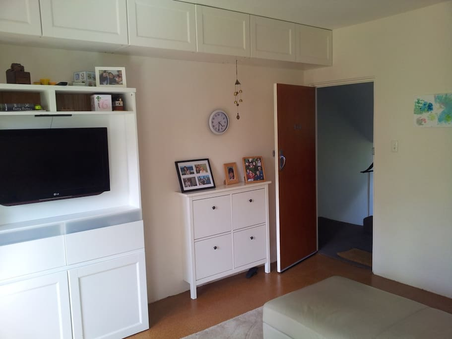 Looking from inside to the entrance showing shoe cabinet and television unit