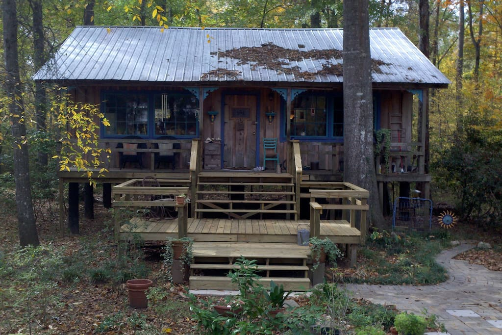 Cabin with deck nested in the hardwoods of the creek bottomland.