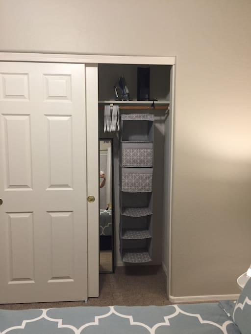 Large closet with hangers, iron, personal fan, long mirror, and extra storage.