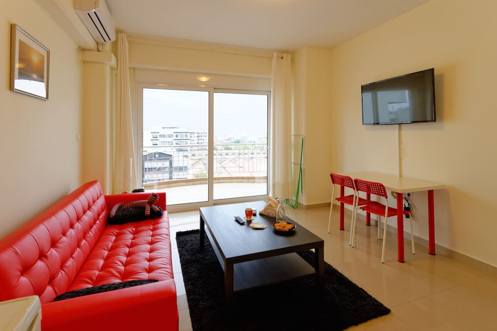 """Living area, with 43"""" TV and large balcony."""