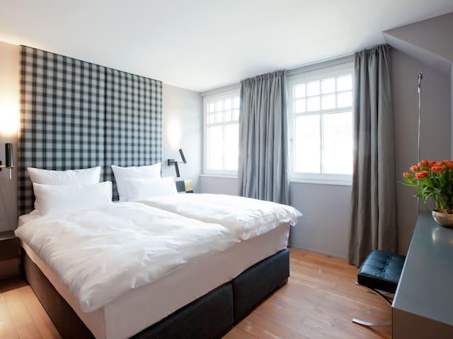 Boxspringbett mit Qualität, Gänsedaunendecken, eben echte Materialien. Schlafzimmer mit begehbarem Kleiderschrank und Flachbildschirm
