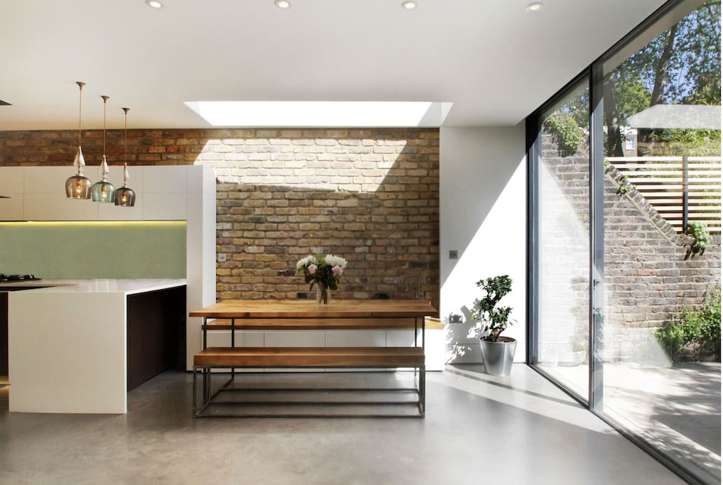 Skylights, sliding doors, exposed brickwork create a lovely environment for relaxing, families and socialising.