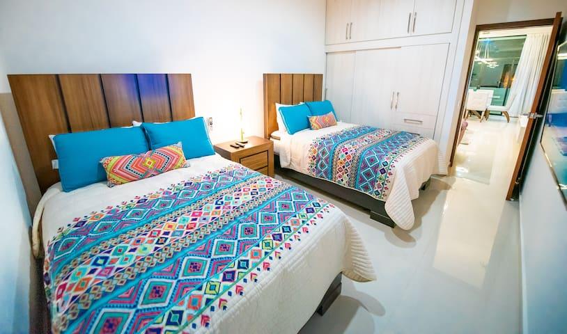 Confortable Recámara principal con baño completo, 2 camas matrimoniales y pantalla plana de 55 pulgadas smartv y sistema de cablevisión, persianas blackout y colchones tope de gama para tu comodidad y descanso