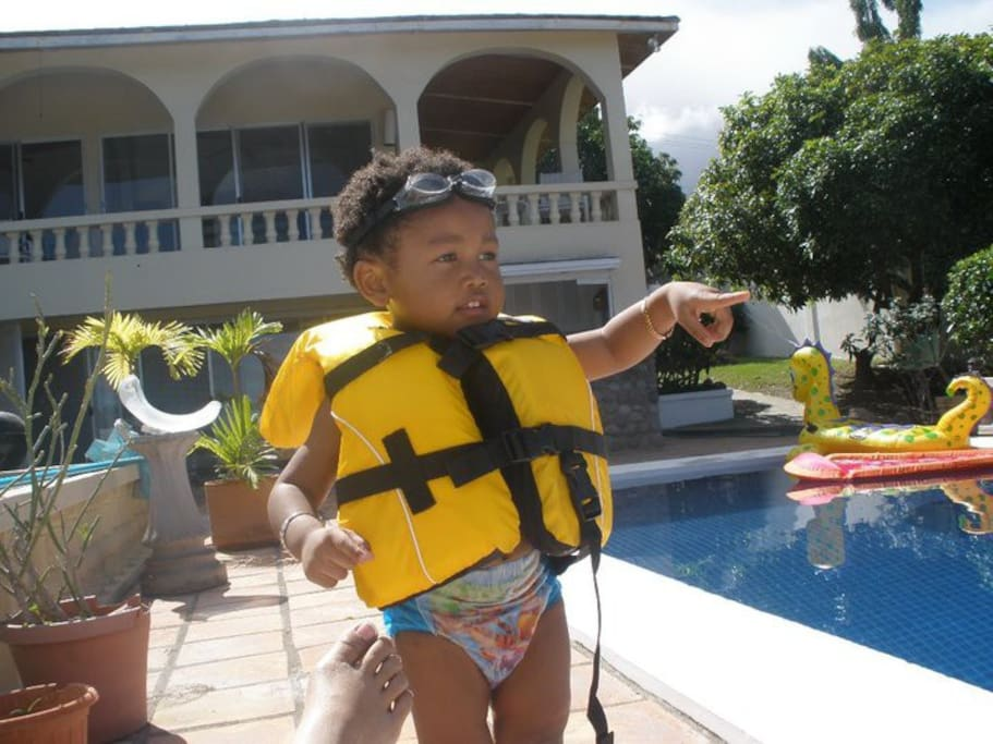 On the pool patio with adult and child life-jackets