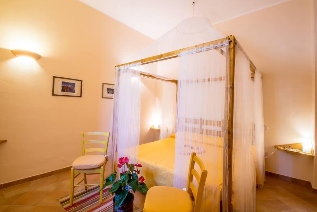 la camera matrimoniale con letto in legno a baldacchino