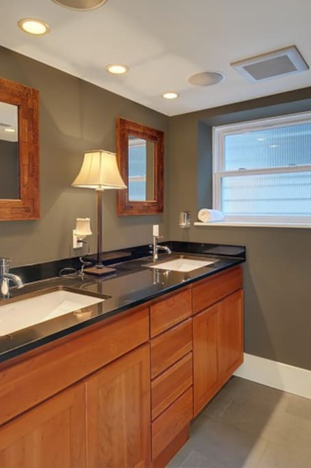 Private 2 sink bath with heated tile floors,cherry cabinetry and granite counters.