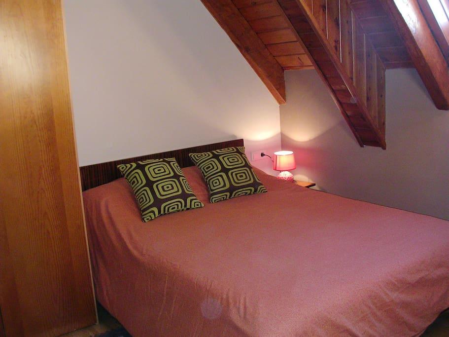 La habitación es abuhardillada con madera ,muy acogedora.