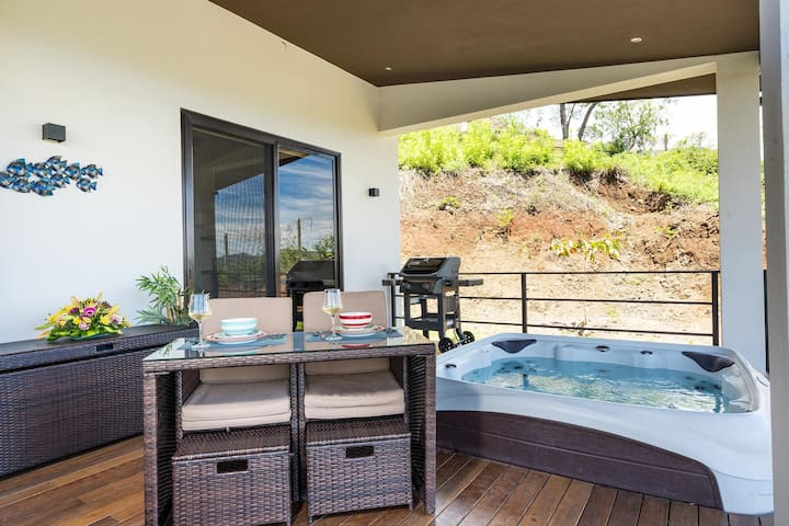 Oversized covered terrace with Jacuzzi, outdoor dining area and loungers
