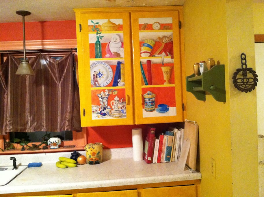 """Kitchen is simple, efficient, certainly colorful, (some might say """"early barnum and bailey),with original trompe l'oeil painted on cabinet."""