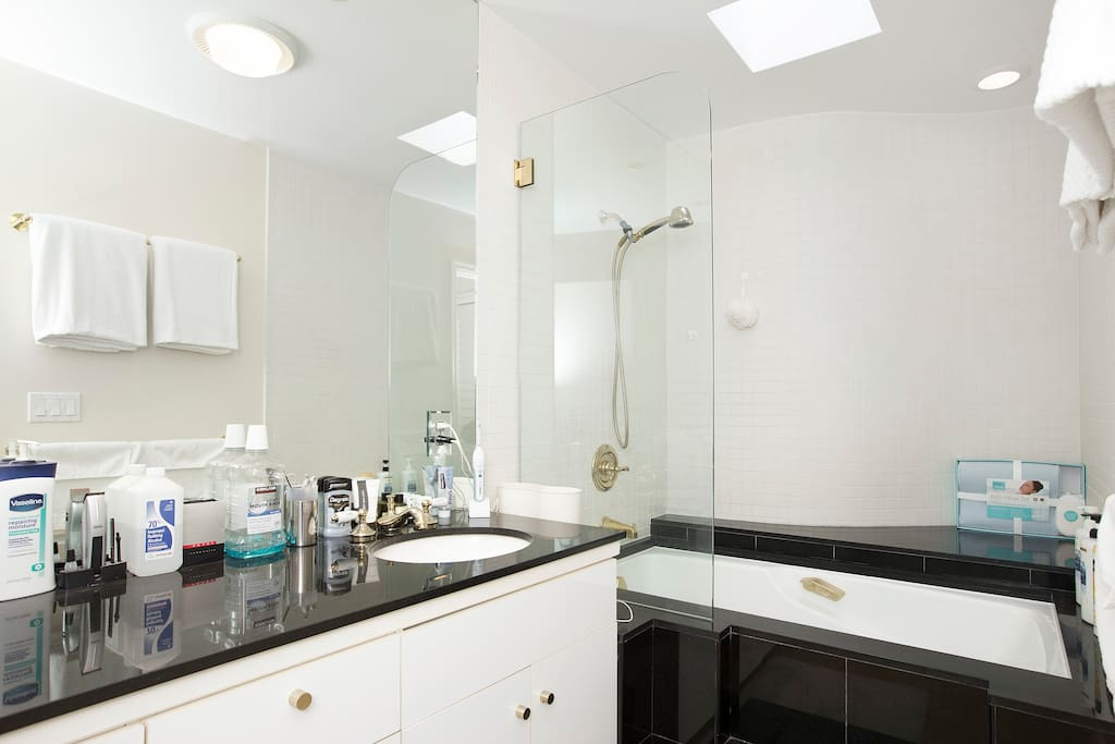 Private bathroom with shower and tub and dual vanity sinks.
