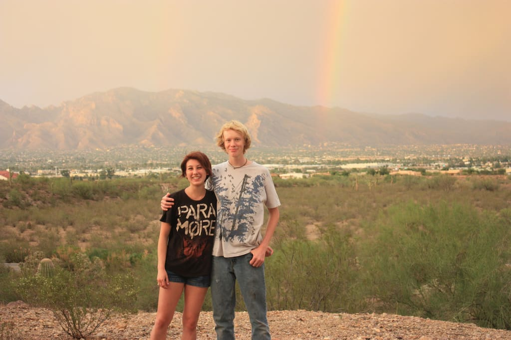 looking north east where my son and friend pose with a monsoon rainbow and Catalina Mts
