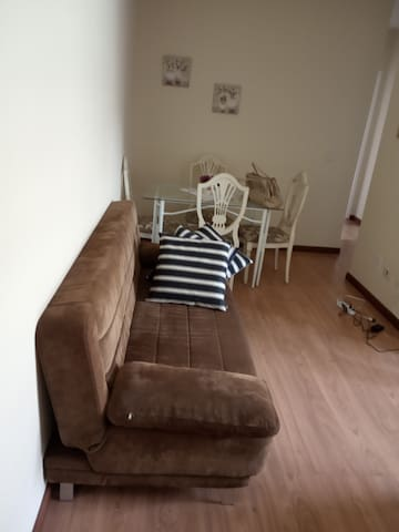 Parte da sala com sofá-cama de casal.
