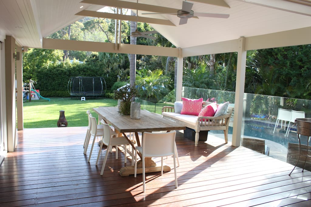 View from kitchen through bi-fold doors to outdoor room, pool and expansive backyard
