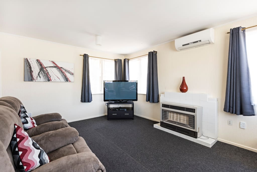 Large TV with a selection of DVDs and comfortable lounge furniture to relax into