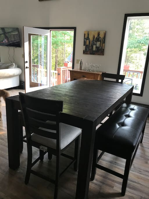 Pub height kitchen table sits 8 (3 per bench) 4 additional barstools on site