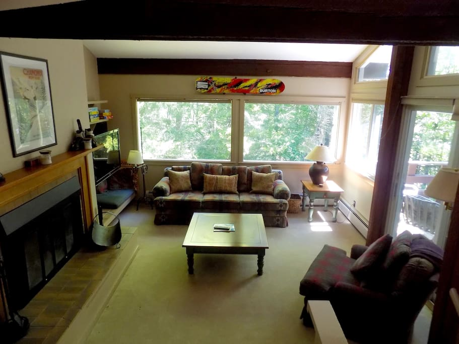 Living room with fireplace and deck, views of Mt. Mansfield's woods