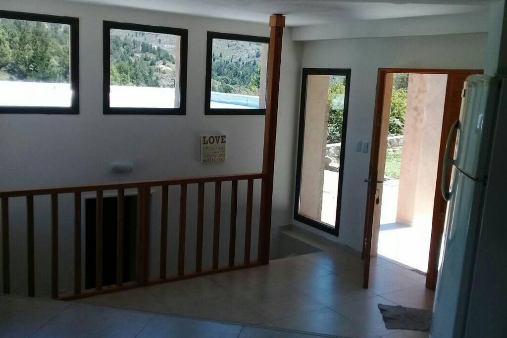 Puerta de ingreso a la casa: a la derecha las escaleras que bajan a los dormitorios. A la izquierda el living con cocina, baño y deck con asador