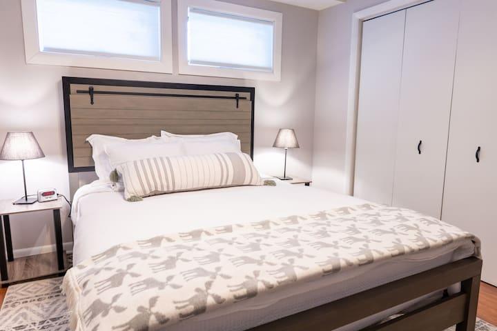 Bedroom #1 features a farm house style queen size bed with an hybrid coil/memory foam Allswell mattress. The windows provide nice natural light and a comfortable setting to relax. USB chargers are provided next to the bed to keep your devices powered up.