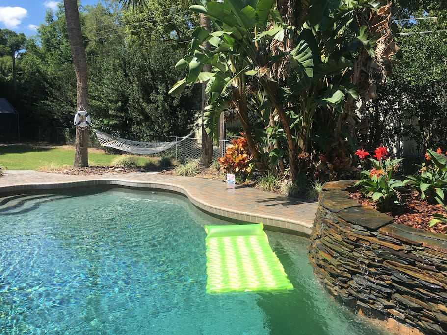 Pool area with hammock between palm trees.