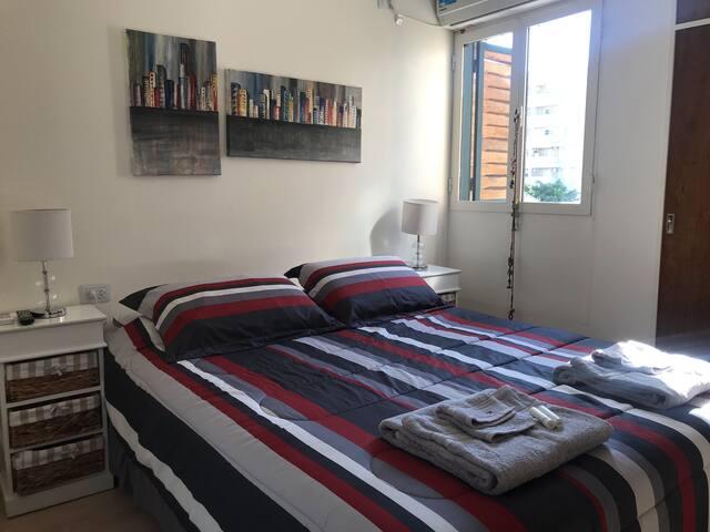 """Habitación matrimonial moderna con muy buena iluminación. Equipada de una cama Queen, Tv 32"""", veladores con su respectiva mesa de luz y armario incorporado"""