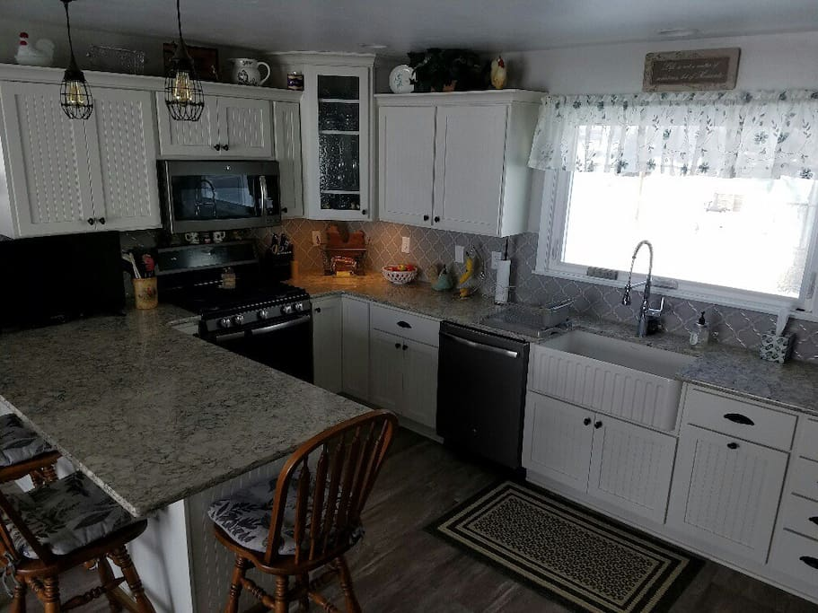 Kitchen with stove, dishwasher, microwave, farm sink, tv.