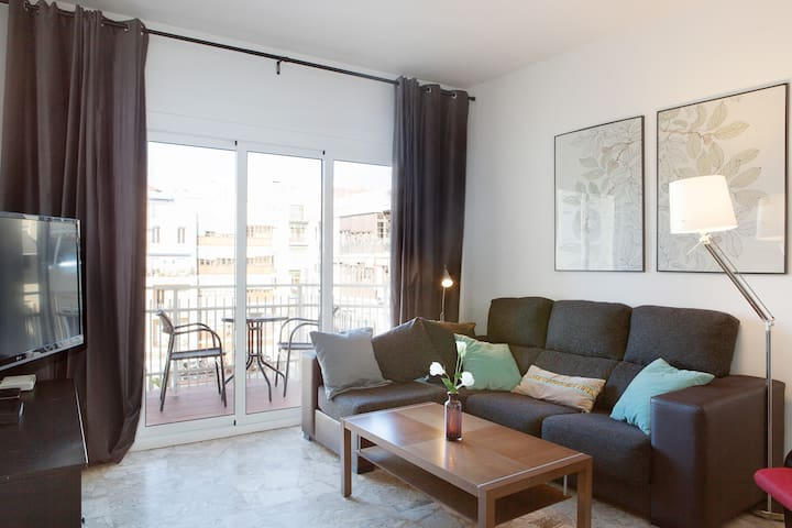 Beautiful living area with large sofa and dinning area with sliding doors out to the balcony