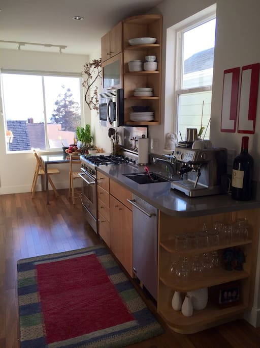 galley style kitchen with dishwasher, microwave, espresso machine and dining area.  4 chairs provided.