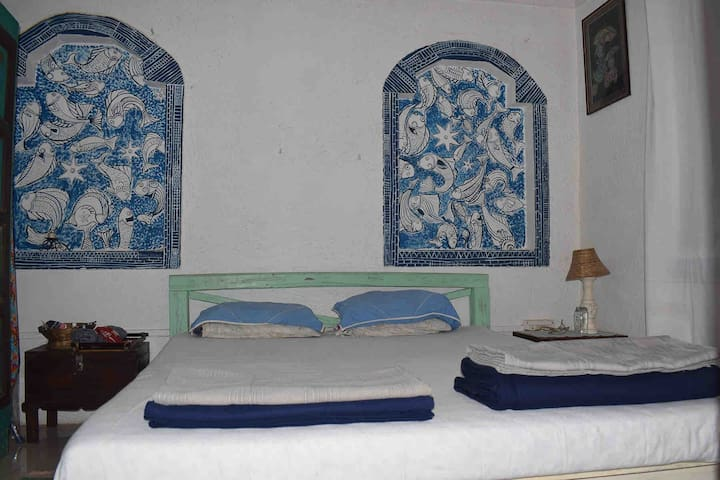 Small white bedroom with handpainted fishes