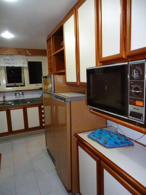 Cozinha totalmente equipada com microondas, geladeira, talheres, panelas e louças