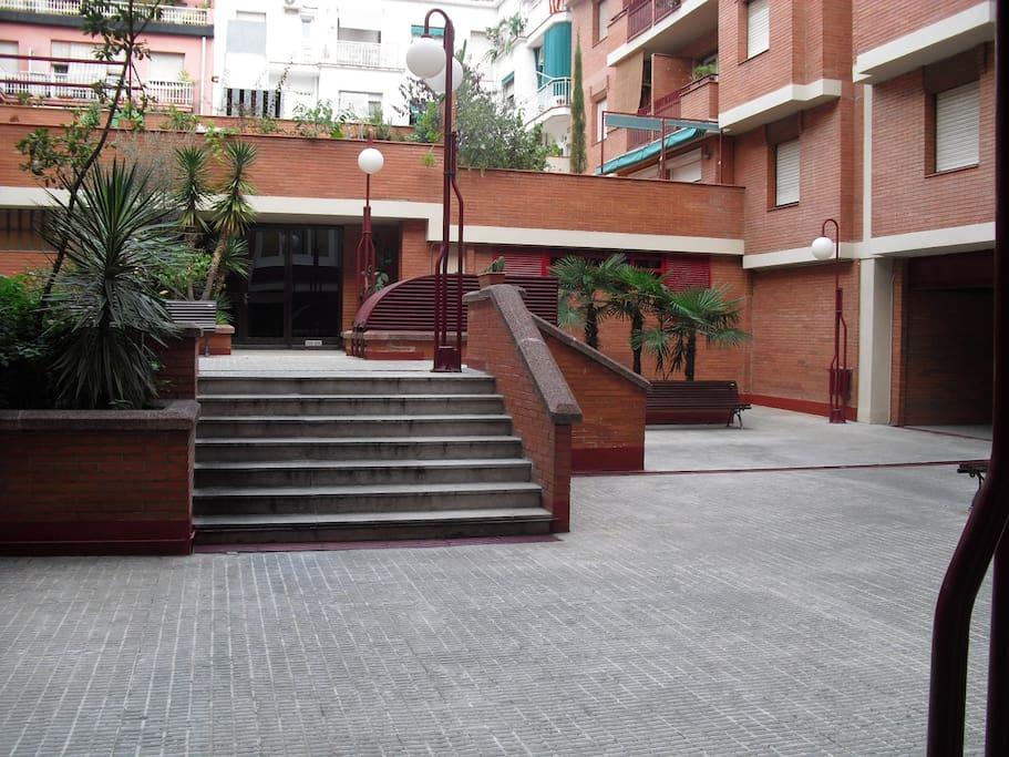 Entrada a la finca por 3 puertas que dan a una zona ajardinada