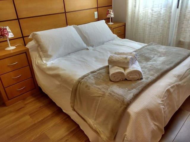 O quarto de casal tem cama queen, é muito iluminado e conta com armário espaçoso e calefação elétrica.