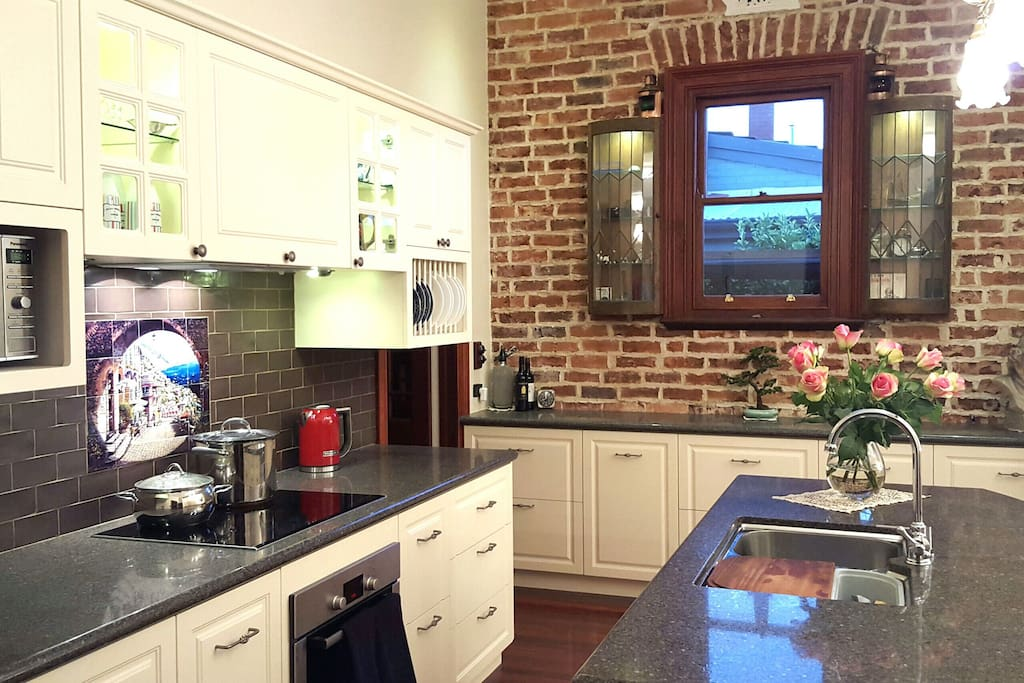 100 year old brick feature wall,  Full modern kitchen, induction stove, microwave, dishwasher