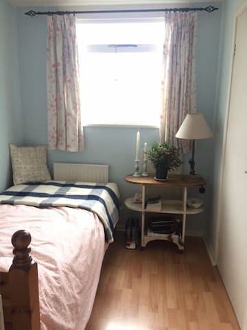 Small single bedroom with fitted wardrobe and bedside table . Shelf unit.   Sunny light room at the front of house, upstairs.