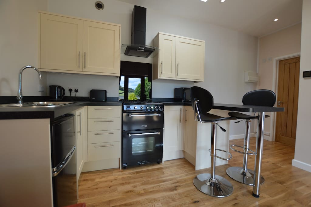 The kitchen has a fridge freezer, microwave, kettle, toaster, extractor fan, gas oven and breakfast bar.