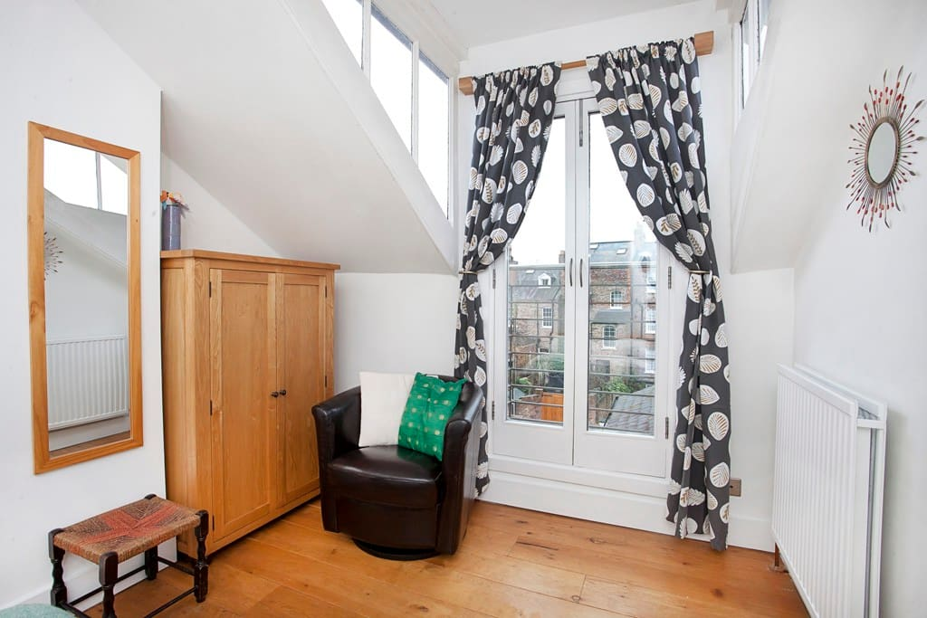Bedroom one with large windows and balcony doors.