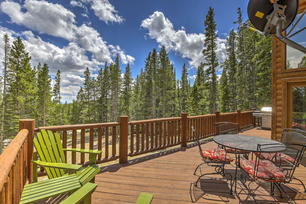 The home features a spacious, furnished deck with peaceful nature views.