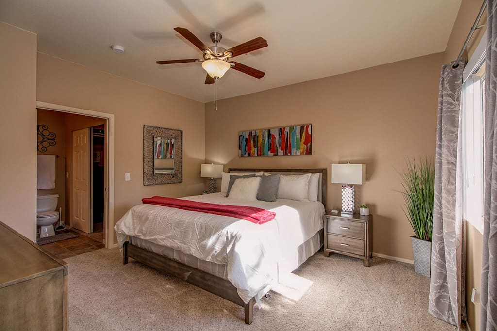 """Master Bedroom with King size bed, 55"""" 4K HDTV, and on-suite bathroom."""