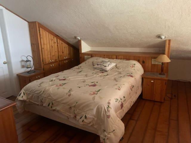 Bedroom in loft overlooking main living area with water views